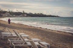 Plastic sunbeds on Tsilivi beach in Zante Island. Woman walking towards the empty white plastic sunbeds on Tsilivi Beach in summer on Zante Island, Greece royalty free stock photography