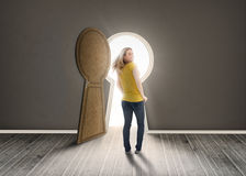 Woman walking towards keyhole shaped doorway with light Stock Photo