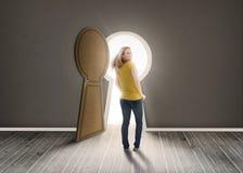 Woman walking towards keyhole shaped doorway with light. Ikn dark grey room Stock Photo