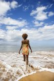Woman walking towards ocean. royalty free stock photo