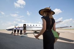 Woman Walking Towards Pilot And Stewardesses Royalty Free Stock Photography
