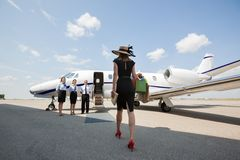 Woman Walking Towards Private Jet At Airport. Rear view of women walking towards private jet while pilot and stewardesses standing at airport terminal royalty free stock image