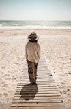 Woman walking towards sea on boardwalk Stock Images
