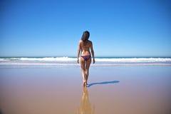 Woman walking towards water at seashore Stock Images