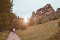 Woman walking through a trail at sunset stock photo