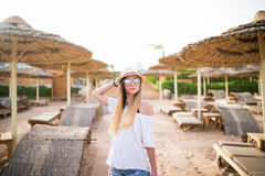 Woman walking on a tropical beach holiday. Luxury wooden lounge and sunny outdoors background Royalty Free Stock Images