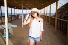 Woman walking on a tropical beach holiday. Luxury wooden lounge and sunny outdoors background Stock Photos