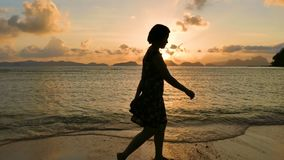 Woman Walking On The Tropical Beach At Sunset. Woman Wearing Dress Walking On The Tropical Beach At Sunset stock footage