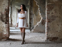 Woman walking trough multiple doors. Beautiful woman walking trough multiple old ruin door frames stock images