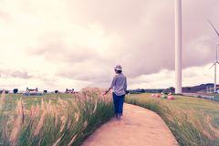 Woman walking in turbine farm Royalty Free Stock Photo