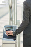 Woman walking through turnstile with pass Stock Photo