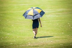 Woman walking with umbrella on fairway in golf course. Woman walking with umbrella on fairway in golf course; sport club Stock Photo