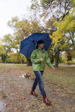 Woman walking with an umbrella in a park with yellow leaves falling from trees. In a city Royalty Free Stock Photography