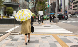 Woman walking with umbrella. Tokyo, Japan - April 8th, 2017: Woman walking in Tokio wearing trench coat, black bag and umbrella with flower pattern Stock Photography