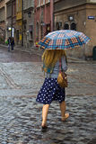 Woman walking with an umbrella. Warsaw, Poland - August 25. Young woman walking with an umbrella in the rain at the old town in Warsaw, Poland Royalty Free Stock Photos