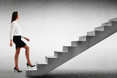 Woman walking up concrete stairs Stock Photo