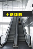 Woman walking up the escalator at an airport. Picture of a woman with her suitcase up the escalator at an airport Stock Photography
