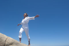 Woman walking up a hill. An attractive looking mature woman dressed in white and with her arms stretched out sideways, is walking up a rocky hill with a smiling Royalty Free Stock Photos