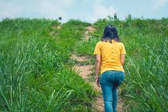 Woman walking up the hill on green grass trail. Woman walking up the hill on green grass trail at countryside royalty free stock photos