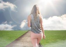Woman walking up path to blue sky sun. Digital composite of Woman walking up path to blue sky sun Royalty Free Stock Image