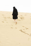 Woman walking up sand hill Royalty Free Stock Photos