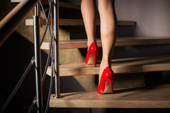 Woman walking up stairs. In red high heels Royalty Free Stock Photos
