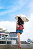 Woman walking up stairs with umbrella as sun protection. Woman walking up stairs with umbrella to protect from the sun Stock Images