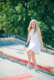 Woman walking upstairs outdoors. Beautiful young blond woman in a white dress walking upstairs outdoors Stock Image
