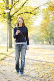 Woman Walking and Using a Mobile Phone Stock Photo