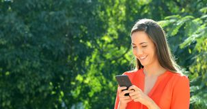 Woman walking using smart phone in a park. Happy woman walking using smart phone to chat in a park