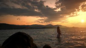 Woman walking in water and looking to the horizon stock footage