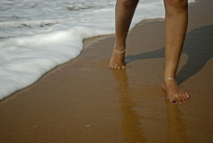 Woman is walking on the water of sea on the beach Stock Photography