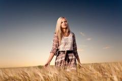 Woman walking on wheat field stock image