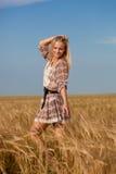Woman walking on wheat field Stock Photo