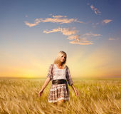 Woman walking on wheat field Royalty Free Stock Images