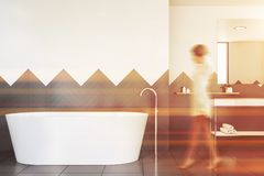 Woman walking in white and gray bathroom. Woman walking in bathroom interior with white and gray walls, tiled floor, white bathtub and sink on white countertop stock illustration