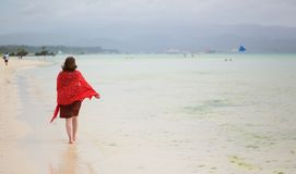 Woman walking by white sand beach Royalty Free Stock Images