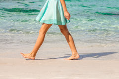 Walking on beach. Sexy woman dressed with green skirt walking bare foot on the beach shore. Closeup of her tanned naked shaved legs. Closeup detail of female Royalty Free Stock Images