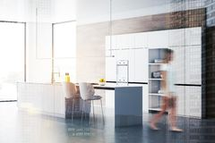Woman walking in white and wooden kitchen. Young woman walking in stylish kitchen with wooden walls, concrete floor, white cupboards and island with sink and royalty free stock image
