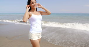 Woman Walking on Windy Beach with Hands in Hair stock footage