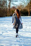 Woman walking in winter park in sunny day Stock Photos