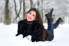 Woman walking in winter snow-covered park. Beautiful young woman walking in winter snow-covered park Royalty Free Stock Images