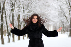 Woman walking in winter snow-covered park. Beautiful young woman walking in winter snow-covered park Royalty Free Stock Image