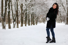 Woman walking in winter snow-covered park. Beautiful young woman walking in winter snow-covered park Royalty Free Stock Photography