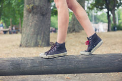 Woman walking on wooden beam outside in park. The feet of a young woman as she is walking on a wooden beam outside in the park Stock Image