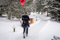woman walking in the woods on a snowy day holding red heart shaped balloon royalty free stock photo