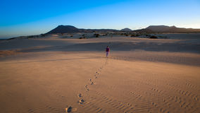 Woman walks alone in the desert. Woman walks alone at sunset in the empty and desolate desert Royalty Free Stock Photography