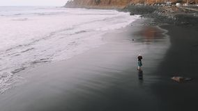Woman walks along the beach, aerial view. Fashionably dressed girl on a black volcanic beach, cinematic top view.