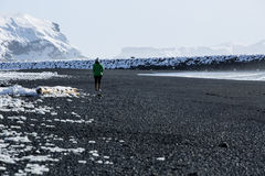 Woman walks along black sand beach in Vik, Iceland Stock Photography