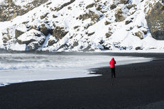 Woman walks along black sand beach in Vik, Iceland Royalty Free Stock Photos